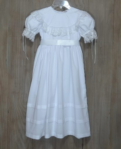 """White batiste dress with a round collar with lace insertion and lace trim . The sleeves can be adjusted with the ribbon ties that run through beading and are trimmed with lace. The waist has a ribbon sash that ties in the back (see picture). The skirt is accented with two 1 inch tucks. By """"La Jenns""""."""