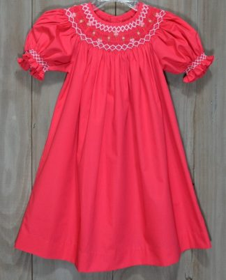 Beautiful coral cotton blend smocked bishop dress with white, pink, and green accent embroidery. By Mom & Me.