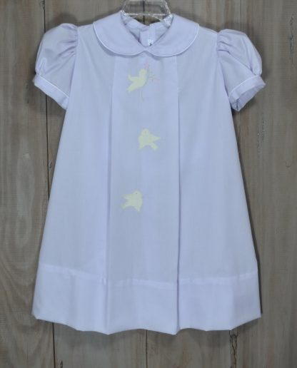 Joanie dress in Lavender Imperial Batiste with hand sewn bird appliques in pale yellow with pink and green embroidered flowers. The collar and sleeves are piped in white. This sweet pattern has been around for generations and is also known as an apron dress
