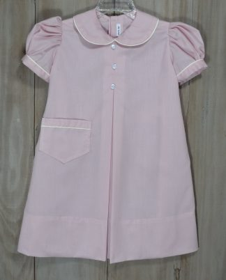 Melissa dress in Prissy Pink, which is mauve colored, accented with ecru piping. It has a pleat down the front and buttons down the back with an accented belt. This sweet pattern has been around for generations and is also known as an apron dress.