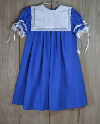 Cailyn dress in royal blue batiste with a white batiste collar with 9 hand sewn pintucks in the center and trimmed in a white French lace. The sleeves have white satin ribbon running through a lace beading and are trimmed in lace.