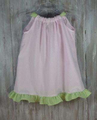 Our handmade Rosie dress in light pink seersucker with lime green seersucker ruffle and ties.