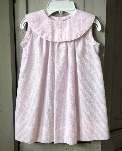 """""""Martha"""" sundress in light pink seersucker with a round collar trimmed in white piping. One of the most popular of our handmade dresses and is ideal for monogramming!"""