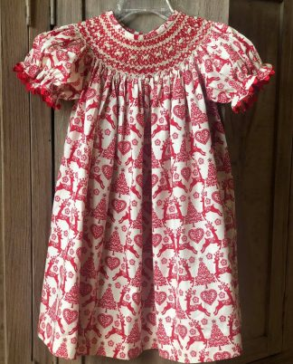 """Bishop dress in ivory and red toile print with reindeer and Christmas trees by """"Banana Split""""."""