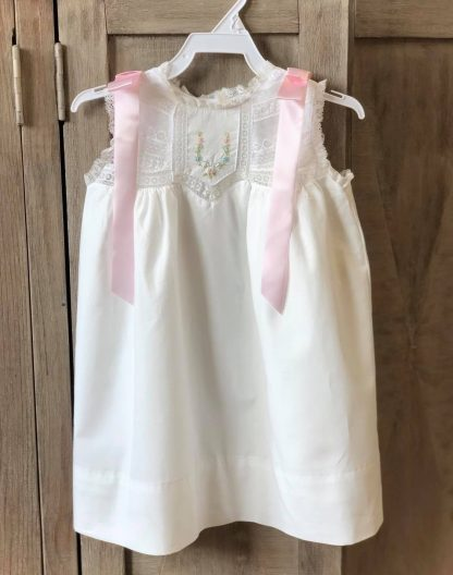 """Heirloom sundress with a variety of lace insertions sewn together for the bodice and a section with a sweet embroidered pattern. The skirt is white 100% cotton batiste with a sewn-in slip. Pink ribbons accent the shoulders for a pop of color. By """"Phoenix & Ren""""."""
