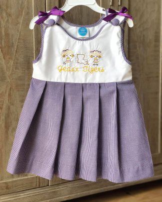 """""""Geaux Tigers"""" pleated purple gingham jumper that buttons on the shoulder straps with accent bows. Show your support for our LSU Tigers in this festive jumper. Although it's supposed to fit on the shorter side it does run shorter than usual. Pair it with a traditional knee sock for a classic look! See the matching younger girl bubble, both are by """"Krewe""""."""