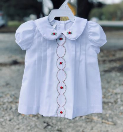 """White batiste dress with tucks and red and green embroidery by """"Baby Blessings""""."""