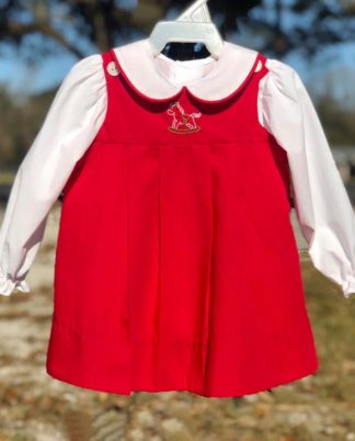 """Red broadcloth jumper with a stitched rocking horse paired with a white blouse by """"Baby Sen""""."""