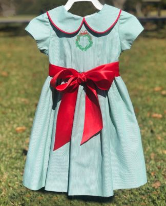 """Green dress with a red satin sash at the waist. The peter pan collar is trimmed in red piping and the box pleat down the center is accented with an embroidered wreath. By """"The Bailey Boys"""". See the matching younger girl look!"""
