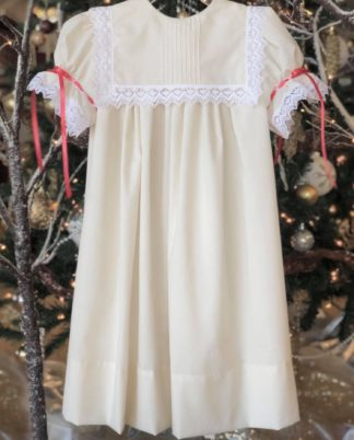 """Beautiful heirloom """"Cailyn"""" dress in Beige Imperial Batiste trimmed in ivory Spanish lace. The collar has hand sewn tucks in the center and the sleeves are tied with red satin ribbon."""