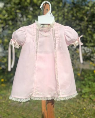"""Pink Batiste dress with tucks and ivory lace insertion and lace trim. There are accents of ivory, pink, and green embroidery and pink ribbon in the sleeves. By """"Baby Sen""""."""
