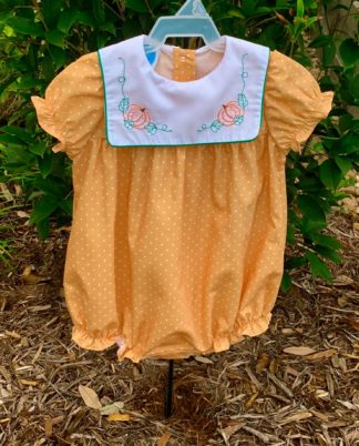 """Sweet Fall bubble in gold fabric with white polka dots and a white square collar with stitched pumpkins and leaves. The sleeves and collar are trimmed in dark green and this bubble is by """"Krewe"""". See the matching toddler dress!"""