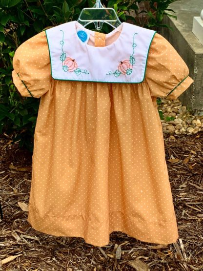 """Sweet Fall dress in gold fabric with white polka dots and a white square collar with stitched pumpkins and leaves. The sleeves and collar are trimmed in dark green and this dress is by """"Krewe"""". See the matching younger girl bubble!"""