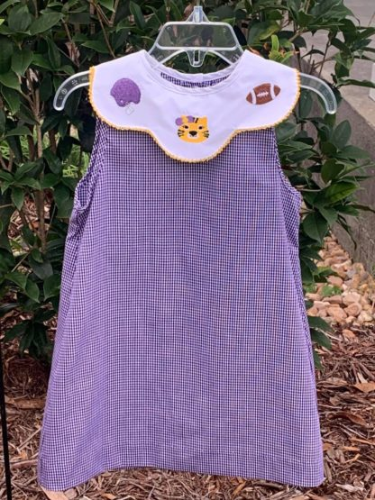 Purple and white gingham A-line dress with a white scalloped collar that is embroidered with a helmet, tiger and football. Perfect for LSU games and tailgating! Geaux Tigers! See matching boy and girl looks!