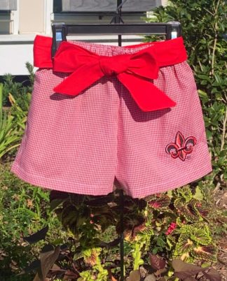 """Red Gingham shorts with a red and black ULL fleur de lis applique' and a sweet sash. See the matching white top. Both are perfect for Ragin Cajun sporting events! By """"Vive La Fete""""."""