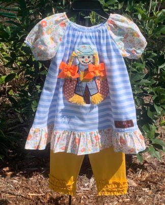 """Light blue and white striped top with a scarecrow applique' paired with a gold legging. Set is by """"Millie Jay""""."""