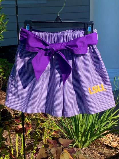 """Purple gingham shorts with the LSU logo and a purple sash by """"Vive La Fete""""."""