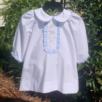 """Beautiful and simple white dress with a placket that is trimmed with a blue ruffle and embroidered in a classic pattern. By """"Bailey Boys""""."""