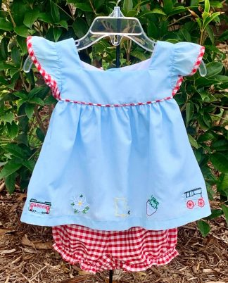 """Light blue top accented with red gingham trim and bloomers with stitched pictures representing the great state of Louisiana! The pictures are of a NOLA street car, the magnolia state flower, the state of LA, a strawberry, and a carriage. By """"Krewe""""."""