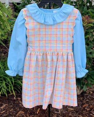 """Plaid jumper dress in the colors of orange, blue, and gold paired with a blue blouse. The scalloped accents make it unique and the back looks just as sweet as the front! By """"Sage & Lilly""""."""